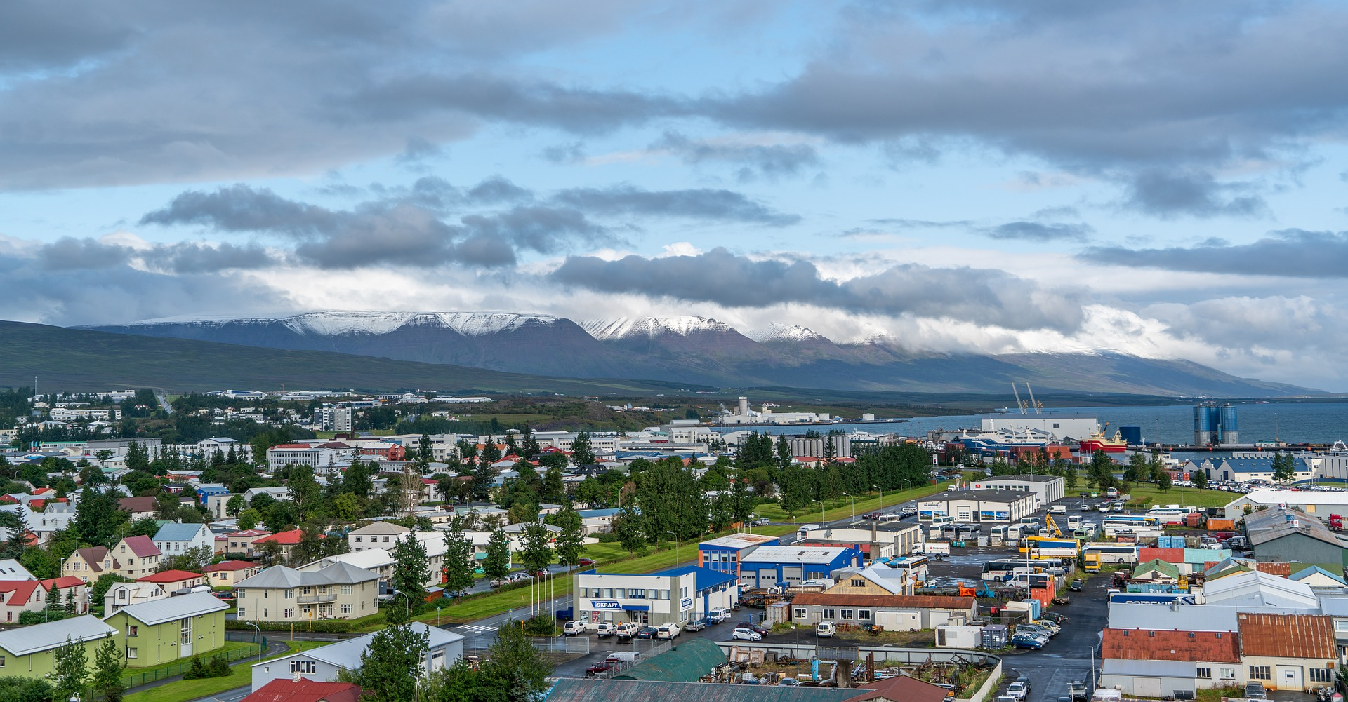 the city of akureyri with colorful houses and mountains on the background