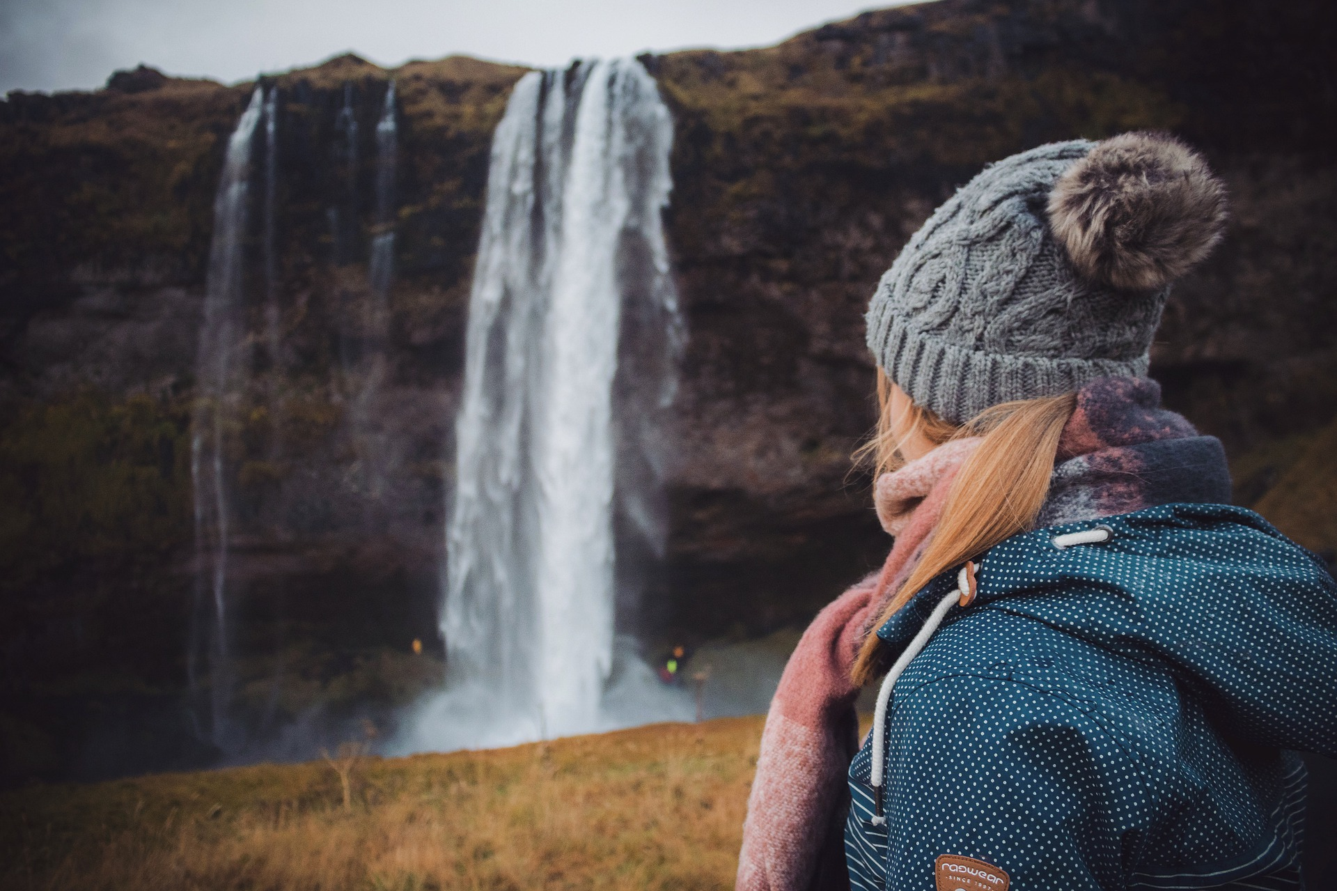 Woman looking at seljalandsfoss waterfall in Iceland