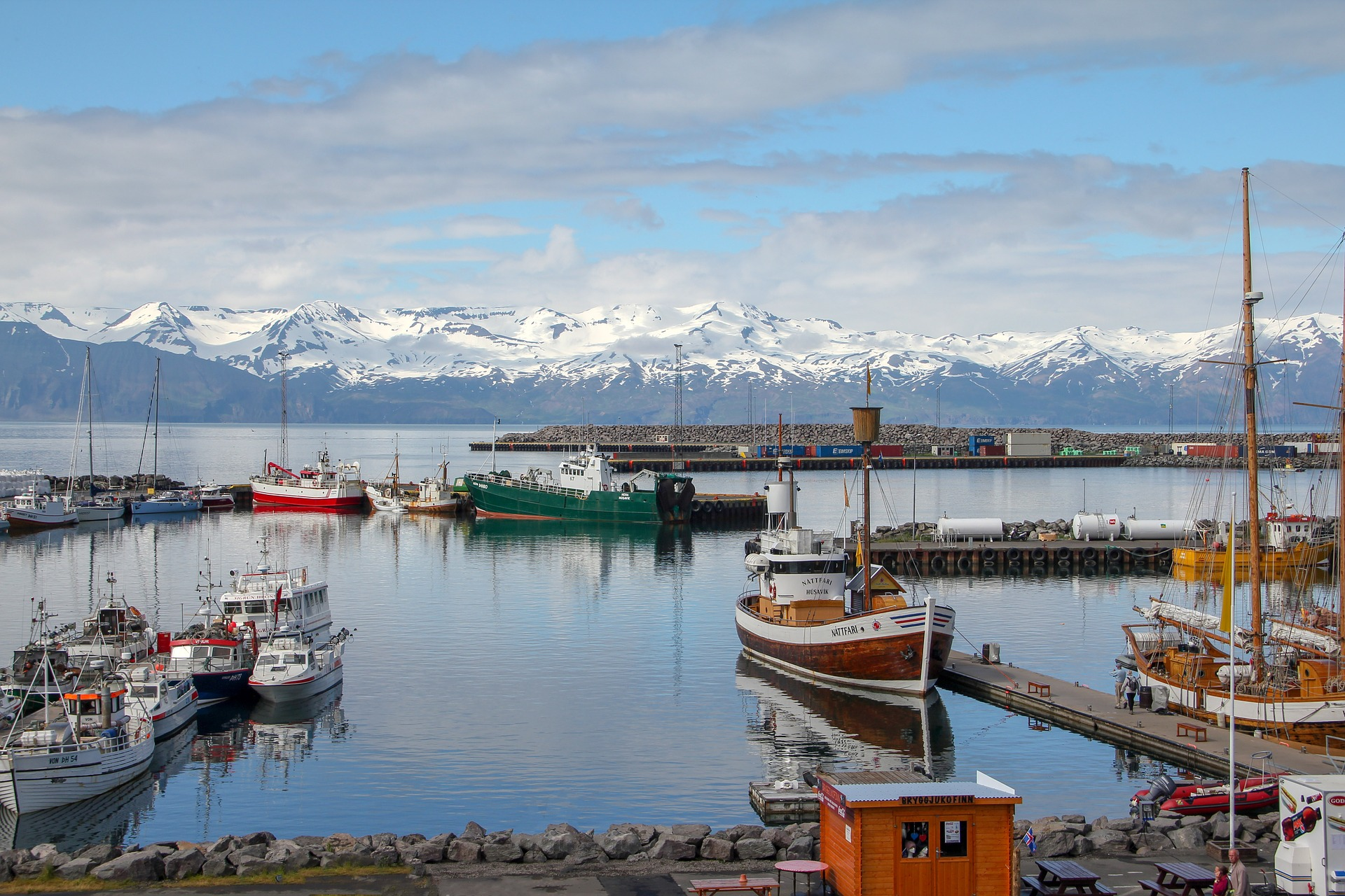 fishing harbor of Husavik with boats, docks, sea, mountains on the background