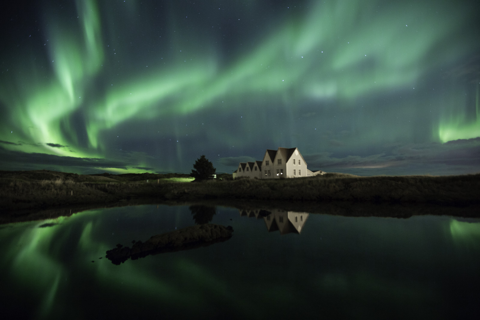 green northern lights with houses