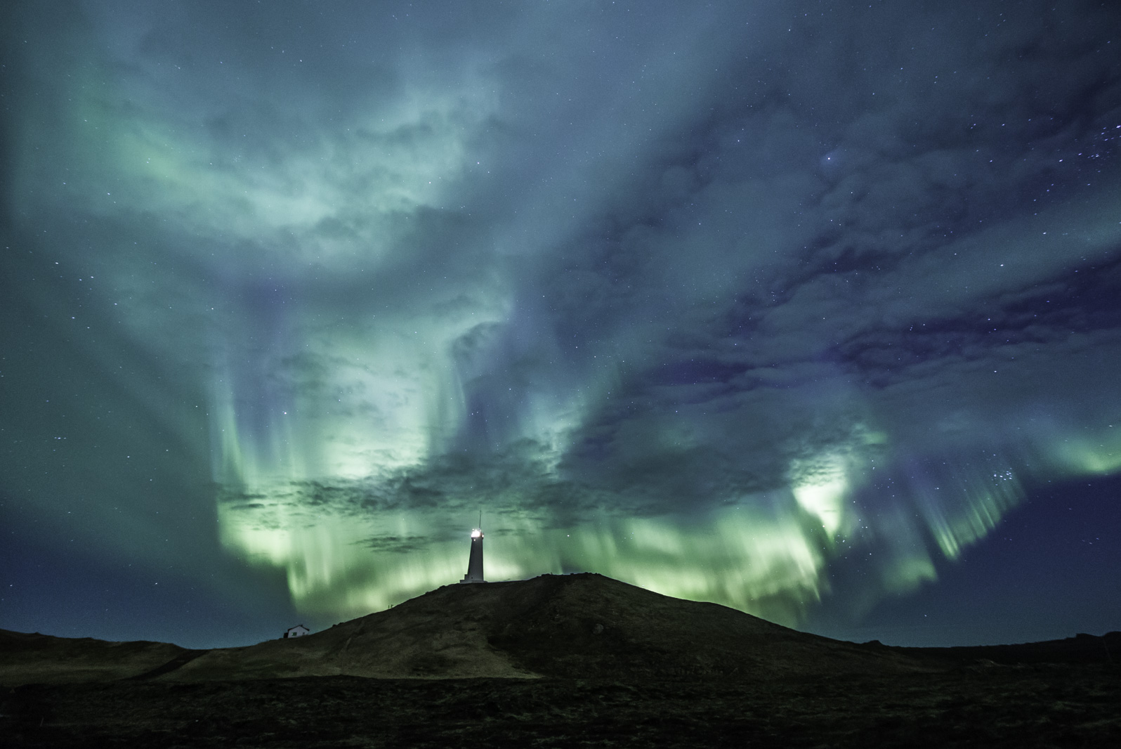 sky filled with blue and green northern lights in iceland