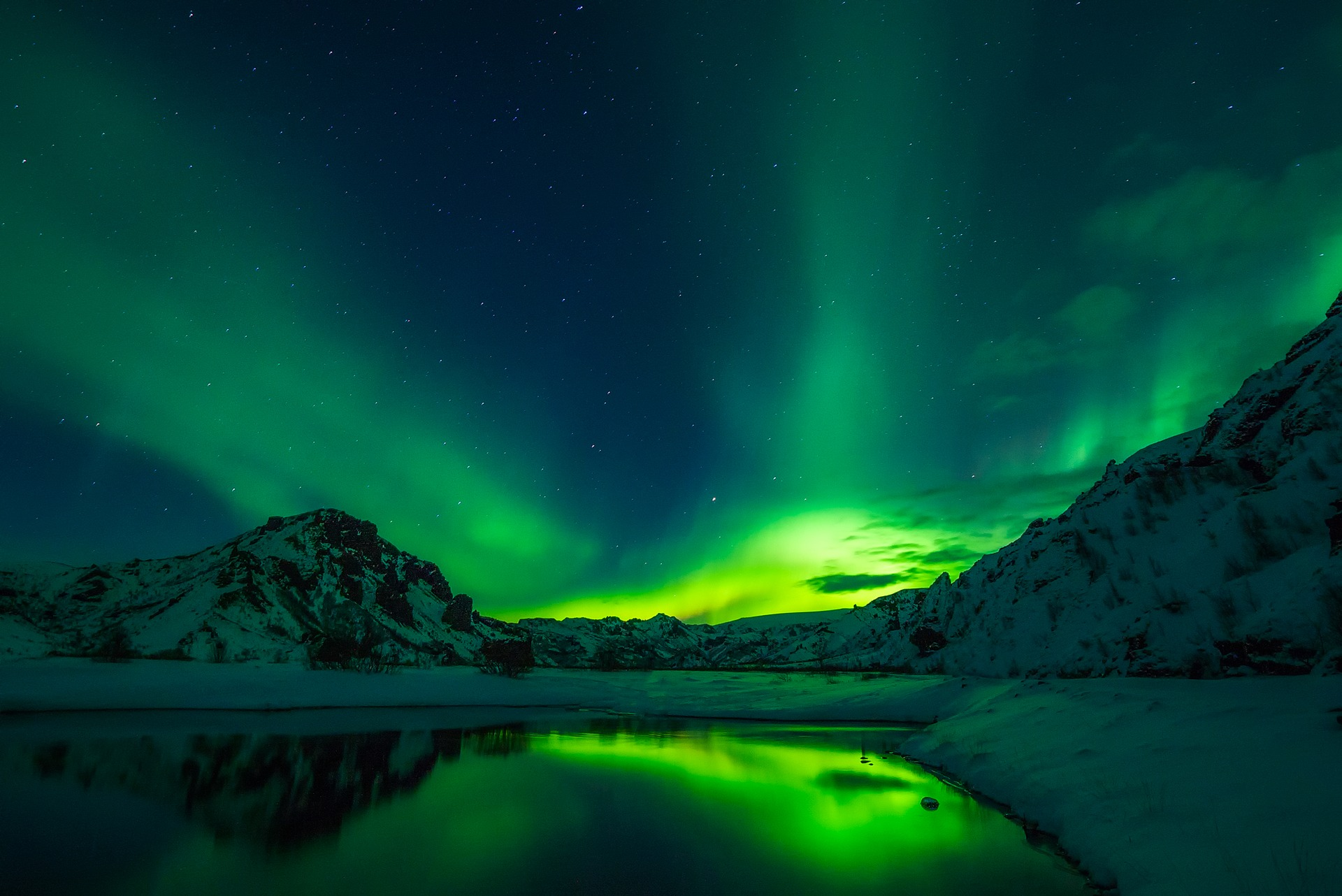 green northern lights above mountains and a lake in iceland