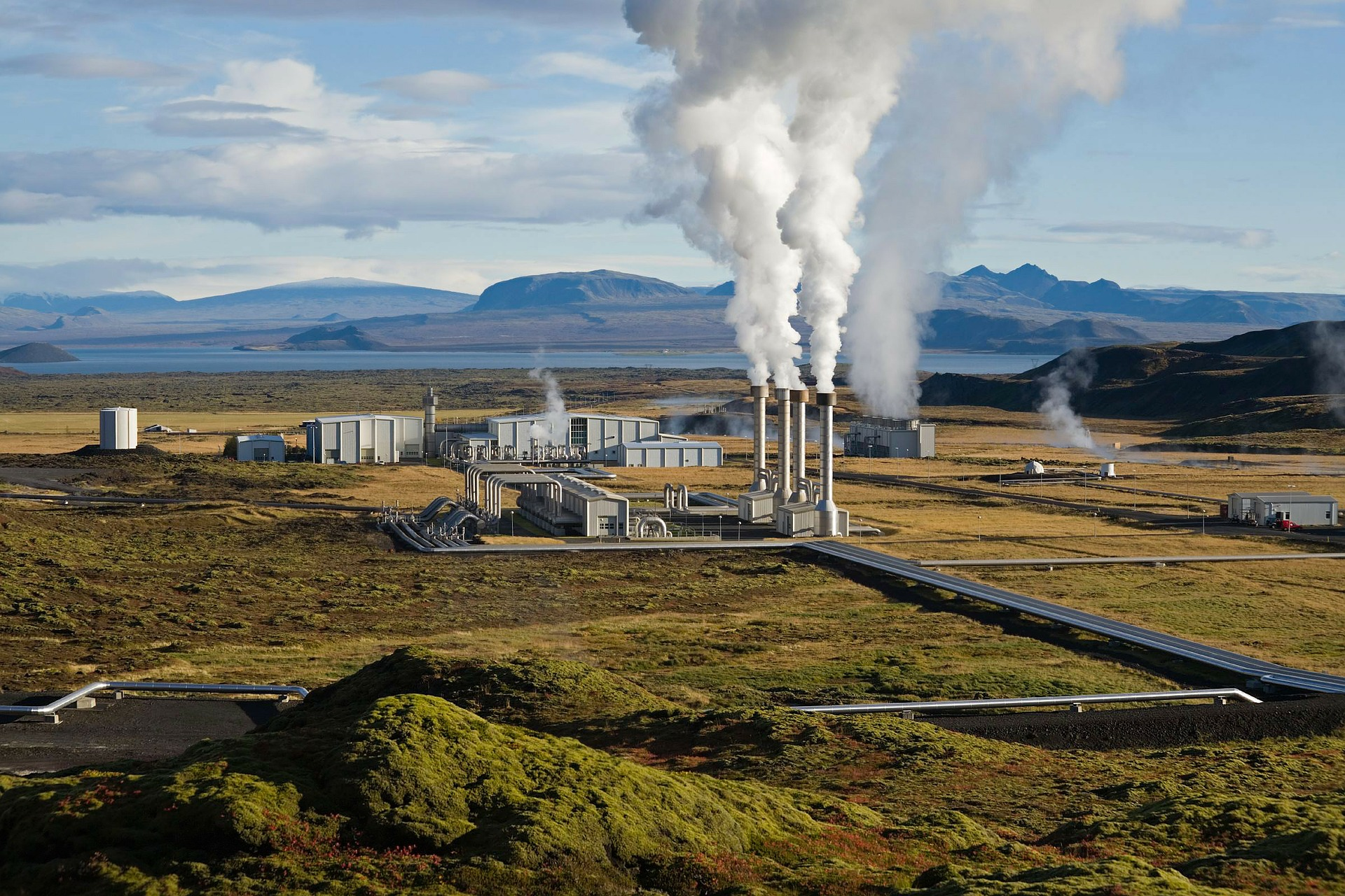geothermal plant in Iceland, green plains, clear blue sky and mountains on the background