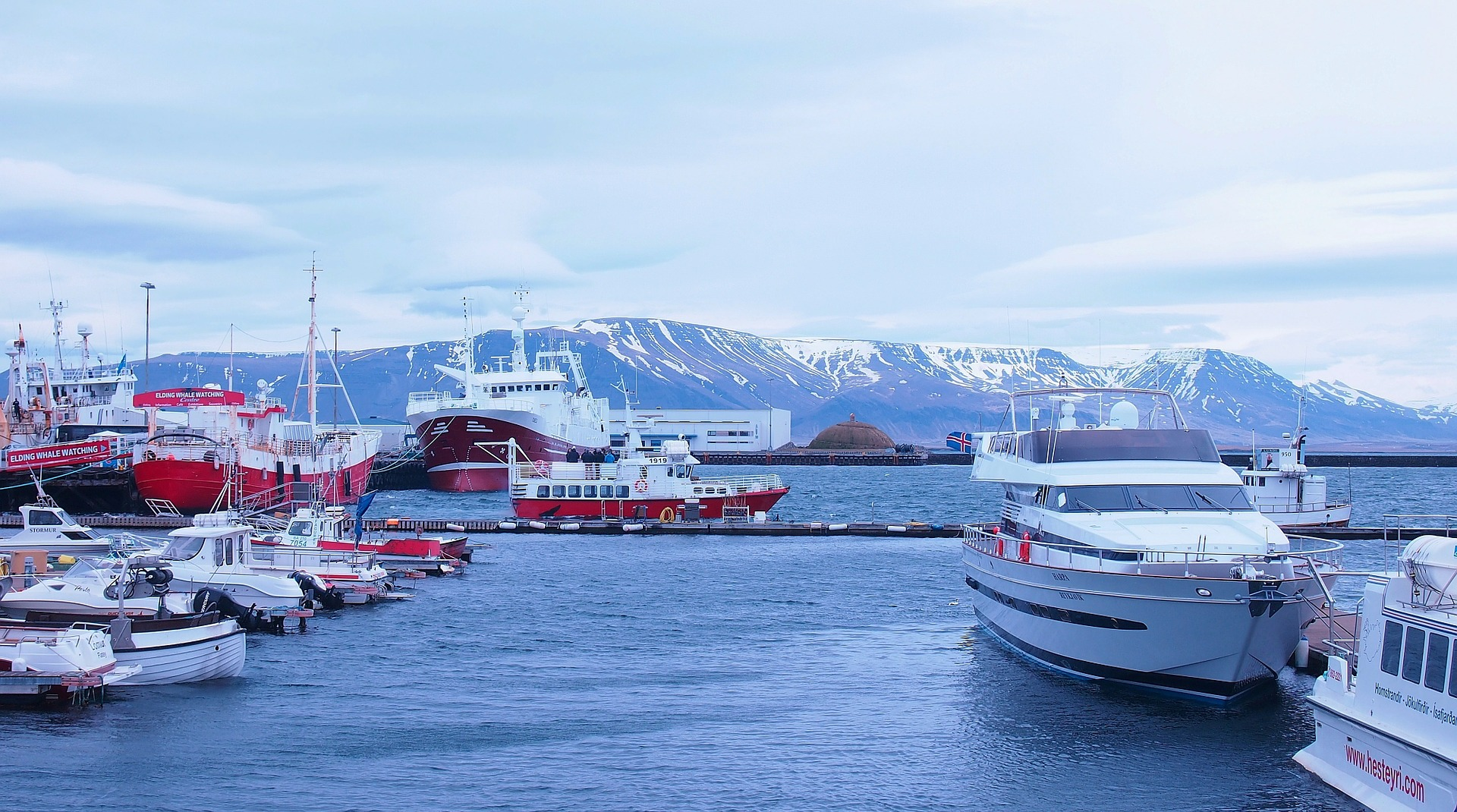 Reykjavik harbor, water body, boats, docks and mountains on the background
