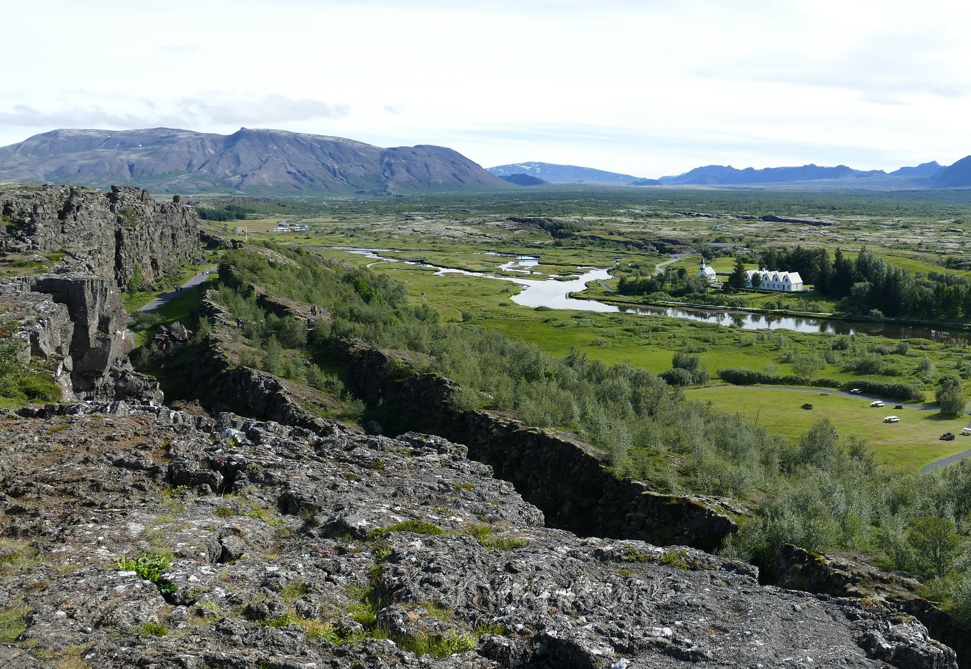 National park of Thingvellir, rocks on the foregroung, grass, tress, mountains on the background