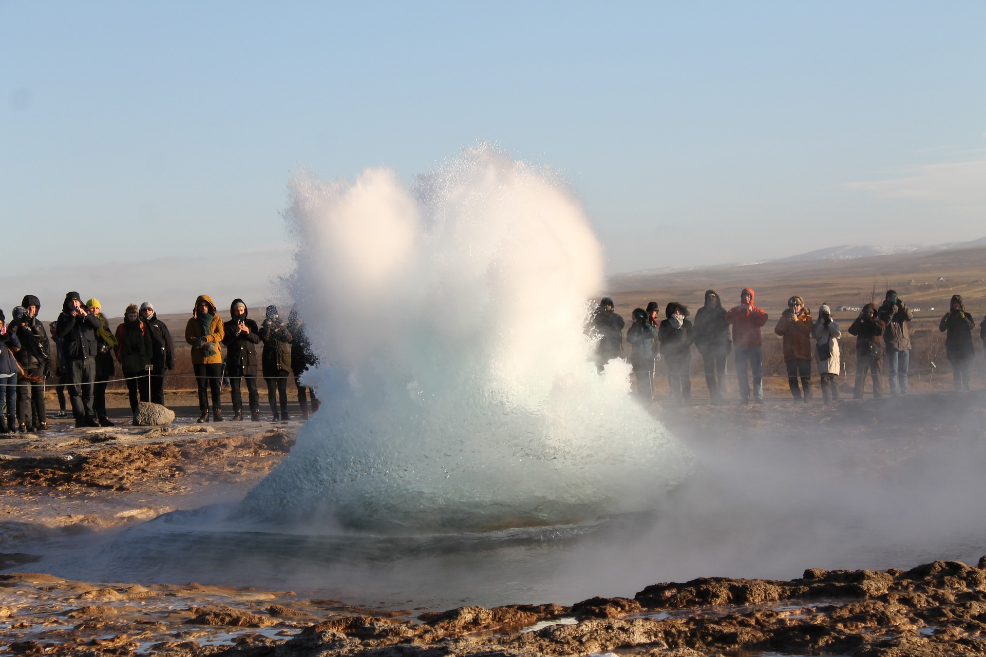 the start of a geyser at Geysir in Iceland, tourists on the background